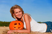 woman in jeans shorts posing on a bale with pumpkin — Foto Stock