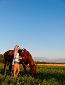 Young girl walking with a horse in the field — Foto Stock