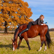 Stock Photo: Beautiful womwalking with horse
