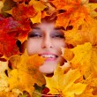 Beauty portrait of beautiful female face with autumn leaves — Stock Photo
