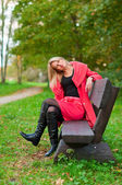 Autumn woman sitting on a bench — Stock Photo