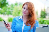 Pretty young business woman using mobile phone — Stock Photo