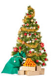 Christmas tree with gifts and mandarines — Stock Photo