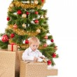 Little boy opening Christmas gift near New Year's tree — Stock Photo #34840401