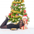 Woman with gift, glass of wine, sushi and christmas tree — ストック写真