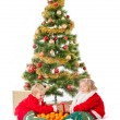 Two little children playing under christmas tree — Stock Photo