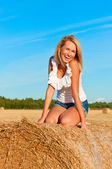 Beautiful woman in  short  posing on a wheat bale — Stock Photo