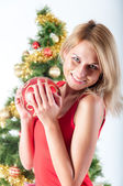 Blond woman holding red christmas ball — Stock Photo
