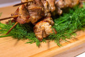 Grill meat on a sticks with green on wooden plate — Stock Photo