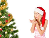 Woman in santa claus hat blows on open hands — Stock Photo