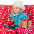 Funny girl around christmas boxes with red ball — Stock Photo #49324693