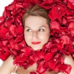 Rose petals around a beautiful womans face — Stock Photo #49326289
