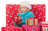 Funny girl around christmas boxes with red ball — Φωτογραφία Αρχείου