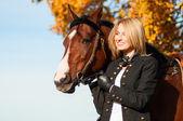 Beautiful woman walking with horse — Stock Photo