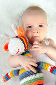 Adorable baby playing with colorful hand made crochet toy on white background — Stock Photo