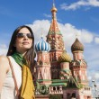 Tourist woman in front of saint basil cathetral in moscow — Stock Photo #13515990