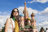 Tourist woman in front of saint basil cathetral in moscow — Stock Photo