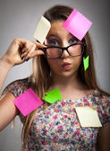 Teenage girl covered in notes — Stock Photo