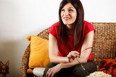 Mujer joven sentada en un sofá — Foto de Stock