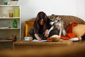 Brunette woman relaxing in living room with Siberian Husky — Stock Photo