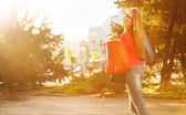Cool girl walking on the street with shopping bags — Stock Photo