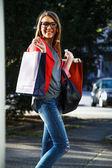 Cool kız alışveriş torbaları ile sokakta yürürken — Stok fotoğraf