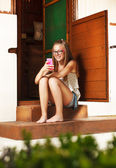 Teenage girl sitting in front of rural house — Stock Photo