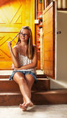 Caucasian girl chilling on wooden house porch — Stock Photo