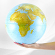 Earth globus in hand, various background — Stock Photo