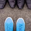 Blue sneakers on asphalt — Stock Photo