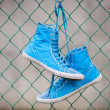 Blue sneakers on fence — Stock Photo
