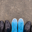 Blue sneakers on asphalt - Stock Photo