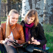 Two young women reading magazine — Stock Photo