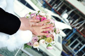 Hands of just married on wedding bouquet — Stock Photo