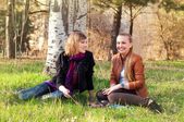 Two young women talking in the park — Stock Photo