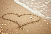 Handwritten heart on sand with wave approaching — Stock Photo