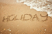"""Handwritten """"holiday"""" on sand with wave approaching — Stock Photo"""