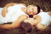 Happy young couple relaxing together on the grass, love concept — Stock Photo