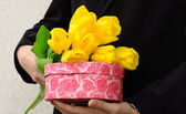 Man in suit with flowers and gift box — Stockfoto