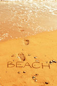 "Word ""beach"" and foot prints on the sand — Stok fotoğraf"