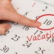 The word vacation is written and circled on a white calendar page — Stock Photo #39542151