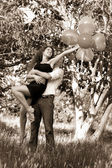 Young couple in love holding bunch of balloons — Stockfoto