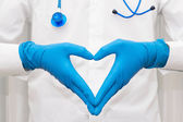 Cardiologist in blue gloves holding his hands in a heart shape — Stock Photo