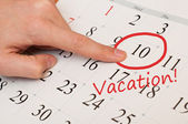 The word vacation is written and circled on a white calendar page — Stock Photo