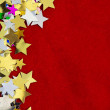 Colorful stars on red velvet background — Stock Photo