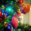 Baubles and lights on Christmas tree - Stock Photo