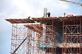 Crane and workers at construction site against blue sky. Thailand — Stock Photo