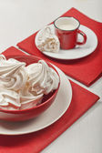 White meringues and a red cup with milk. — Stock Photo