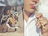 Sweet sticks and smoking man — Stock Photo