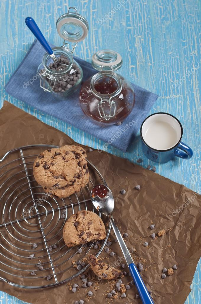 Top view of cookies with chocolate drops on round iron stand and brown paper,cup of milk,  jars with jam and chocolate on cracked blue background — Stock Photo #16350955